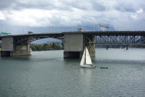 A sail boat sailing (it is what they do best) on the Willamette River in Portland.